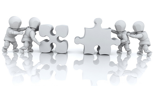 "alt=""Four people trying to push two puzzle pieces together."""