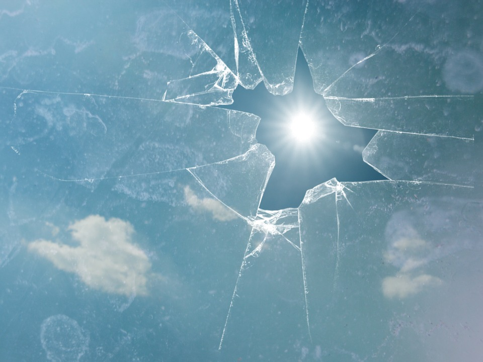 "alt:""A shattered window with the sun peaking through the whole in the glass. Clouds can also be seen in the blue sky. """